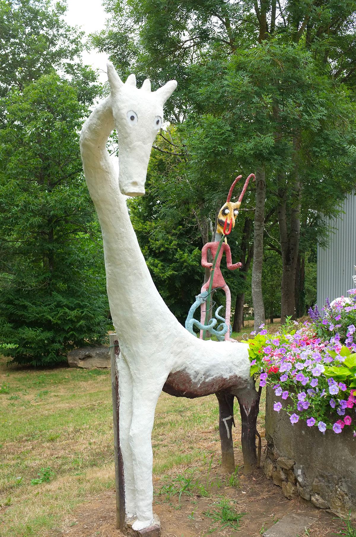 Girafe albinos et son diablotin sur son dos, jardin d'art brut de Fyé